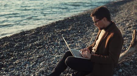o : Freelancer is working remotely, using notebook. He is sitting on open air in evening in sunset near waterfront, surfing the internet