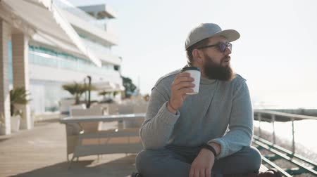 veranda : Hipster man with beard is enjoying cup of coffee in morning near ocean. He is sitting crossed legs on a bench in open air veranda of restaurant