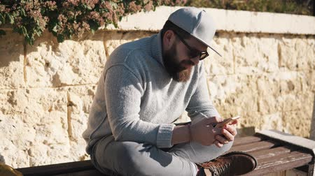 o : Bearded guy is looking on a screen of his phone and watching news tape. He is sitting crossed legs on wooden seat , outdoors in sunny summer day