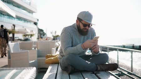 veranda : a young man, dressed as a hipster, sits on the table of a summer veranda by the coastal cafe, he holds a mobile phone and communicates with friends in the autumn time