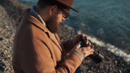 o : a young man with a thick beard is near the sea, the person sitting on the shore and holding a camera in his hands, he looks at the photographs