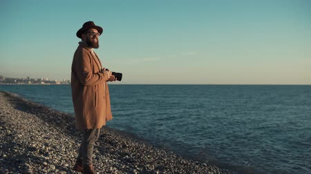 o : a young photographer with a thick beard is like a hipster, a man is holding a modern camera with which he takes photographs, people are wearing a coat and a hat on his head Stok Video