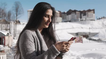 adresa : Young woman with dark hair is typing on keyboard of her smartphone. She is standing outside in sunny winter day in countryside