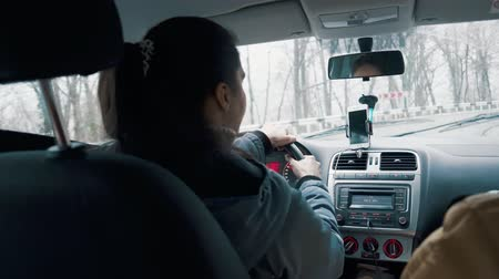 cabins : Shot from behind of a woman sitting behind steering wheel and driving. She is using gps on smartphone.