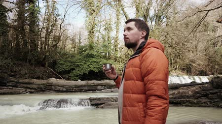 manos mágicas : Inspired young tourist is enjoying a nature and view of wood and stream in autumn day. He is holding metal cup in hands and drinking Archivo de Video