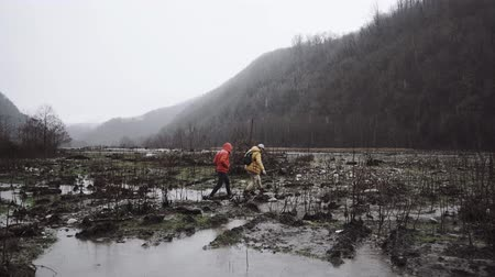 homály : a couple of men walk through the swampy terrain, people try to cross the field with large puddles, high mountains are in a fog, its raining outside Stock mozgókép