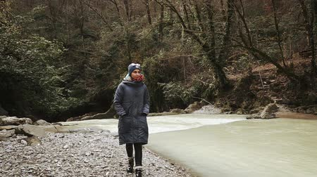 solitário : Lonely woman is walking over woodland in autumn day. She is moving along muddy mountain stream and looking to sides, holding hands in a coat