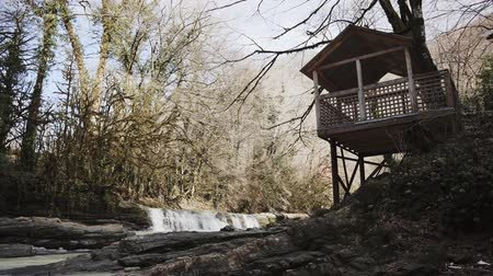 observation deck : View on a landscape of fall forest with wooden survey platform. Small waterfalls on a river flowing between bare trees, sun is shining on tops Stock Footage