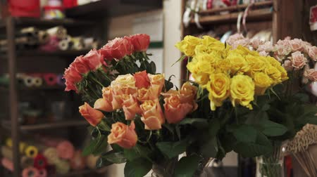 yellow flowers : Rose bouquets in a vase in a floral salon. Flowers are standing in water for saving freshness, for making floristic compositions Stock Footage