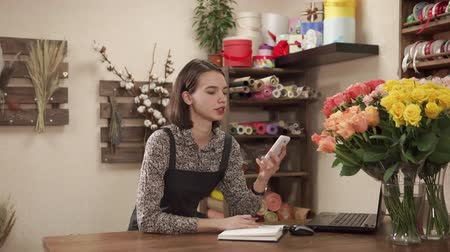 szállító : Managing director woman of floristic shop is calling by mobile and doing notes in a book. She is accepting orders from customers on a delivery of flowers Stock mozgókép