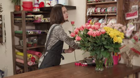 arranging : Floral artist woman is creating a bouquet of beautiful pink rose. She is taking it from vase and lying in her hands, working day in a floral shop
