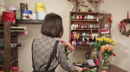 組み立てる : Slim girl is creating floristical composition for sale in a shop. She is taking by one flower and attaching to other 動画素材