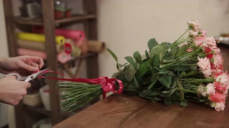 decorador : Floral artist is packing flower composition by ribbon. Womans hands are using scissors for cutting edges, close-up Stock Footage