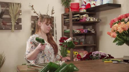 decorador : Young saleswoman is making bouquet of flowers in a workshop. She is taking plants from vases, tearing leaves and gathering it