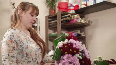 střih : Female salesperson in a floristic store is wrapping a bouquet of vivid flowers. She is lying it on a table and fixing by tape, view of her friendly face