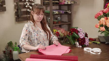 chrysanthemum : Designer florist is preparing wrapping paper for flowers. She is lying in on a table and cutting by scissors, floral decor is lying near