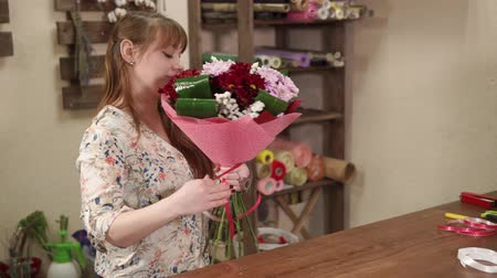 decorador : Woman is packing beautiful flowers for customer in a workshop of floral studio. She is wrapping it by tape and decorating, having a little smile Stock Footage