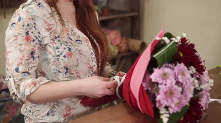 decorador : Female hands is fastening white ribbon on a floral bunch, close-up. She is making flowers decorations for order in a small floristic shop Stock Footage