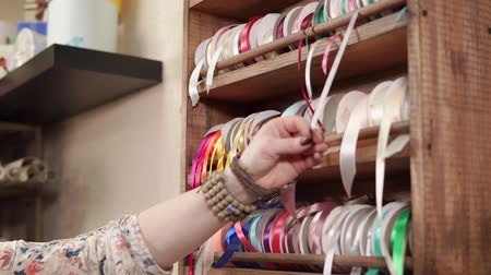 тянущий : Woman is trying different ribbon for packaging, extending it from rack. She is choosing one red tape and cutting a piece of it Стоковые видеозаписи