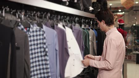 vállfa : Young guy is searching a jacket in a store. He is touching fabric of it and looking on prices in a sale area Stock mozgókép