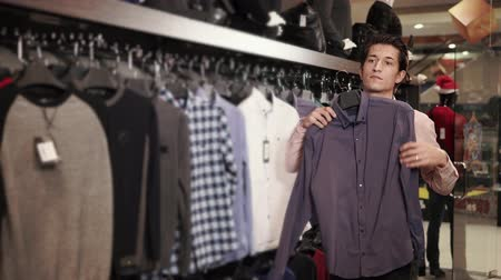 iyi giyimli : Nice looking man is shopping for classic shirts in the mall. He is putting one shirt to his body. Stok Video