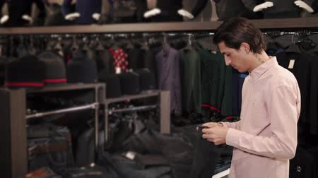 atualizar : a young man with a tattoo on his neck examines black stylish jeans, people choose clothes in order to update the wardrobe in the new season, he holds a pair