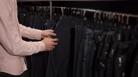 sell : Close up shot of a man looking for a decent pair of jeans in shop. He is taking different pairs and checking them.