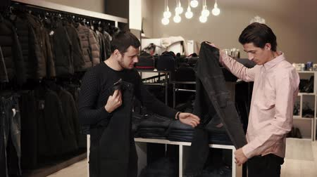 kiállítási terem : a young man with a tattoo on his neck examines black jeans for a purchase, the seller of clothing stores helps to choose the right style and size for the visitor Stock mozgókép