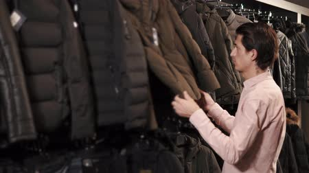 gruccia abiti : a young and thin man considers winter jackets in a clothing store, a man carefully studies the quality of fabrics, maybe he wants to pick up quality and stylish clothes