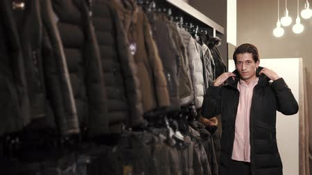 iyi giyimli : Handsome young man is trying on a winter jacket in a shop. He is looking in the mirror and posing,