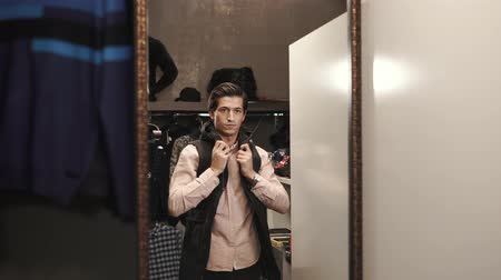 ドレッシング : Handsome stylish guy finds winter waistcoat in a boutique. He puts it on and looks in the mirror. 動画素材