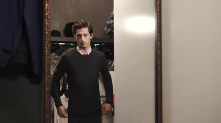 denemek : Shopper is in a fitting room of male clothes store. He is looking on his reflection in a large mirror and correcting fabric of pullover
