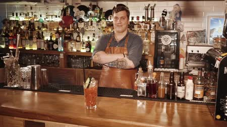 bloody hands : Russia Rosa Khutor - February, 2018: the satisfied barman is standing behind the bar and demonstrating a prepared cocktail with tomato juice, this is an alcoholic drink