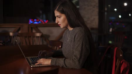 levelezés : Pretty brunette woman working on a laptop in a restaurant in late evening. She is concentrated and serious.