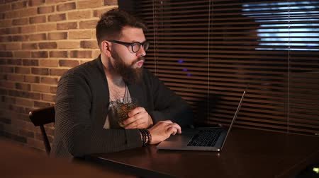 correspondência : Handsome man with beard wearing glasses working on a laptop in a cafe. He is drinking alcohol cocktail.