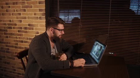não alcoólica : an adult man with a beard and glasses on his face sits at a table in a bar, people looking at photos on his laptop and giving pleasant memories, in his hand a glass of alcohol Stock Footage