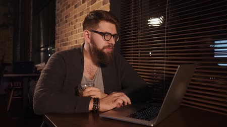 non kentsel : an adult man who is in a cafe enthusiastically looks at a laptop monitor, which stands on the table, the person holding a glass of alcohol in his hand