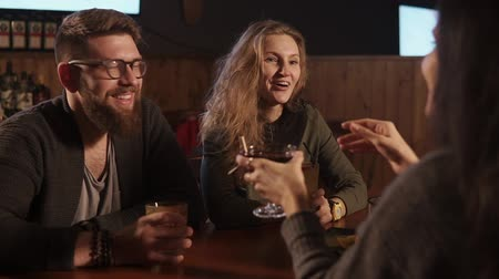 stories : Man and woman are listening their friend girl sitting in a restaurant. They are surprised and answering, drinking alcoholic cocktails