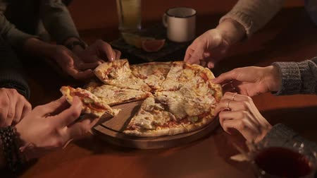 não alcoólica : close up shot of the pizza that is on a tray on the table, a group of men and women take a piece of mouthwatering food, next to them are glasses with drinks Stock Footage