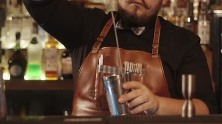 utánzás : Close up shot at work of a professional bartender in a restaurant wearing leather apron. He is using shakers mixing alcohol. Stock mozgókép