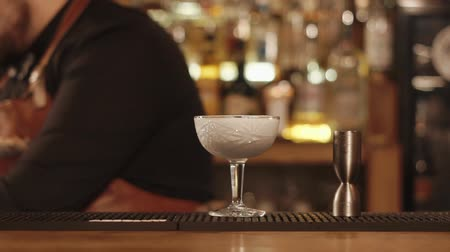 shaker : Barman is pouring white cocktail in a goblet in a bar of restaurant. He is putting paper decor on an edge of glass and moving it forward