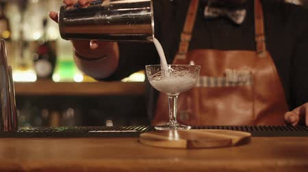 シェーカー : close up shot of the bartenders hands, who makes an alcoholic cocktail in the bar for visitors, the person pours a drink into a beautiful glass goblet 動画素材
