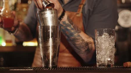 シェーカー : Close up shot at work of barman with a sleeve tattoo in a restaurant. He is making a cocktail using shakers.