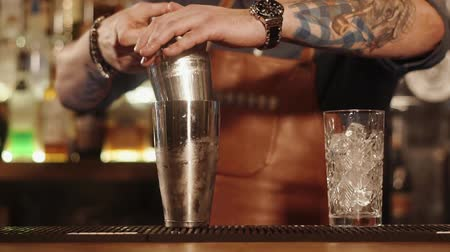 ginástico : Barkeeper is making drinks in a bar, filling bowl by ingredients in a bar. He is having tattoos on his strong hands, close-up view Stock Footage