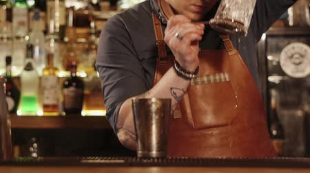 シェーカー : Skillful barman finishing cocktail at the cafe. He is pouring out ice water and pouring in a cocktail.