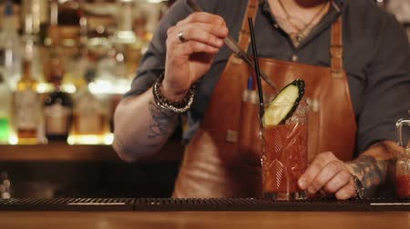 behind bars : Man working in a bar is putting cucumber on a mixed drink like a decor. He is putting it on top and standing behind crossing arms, close-up Stock Footage
