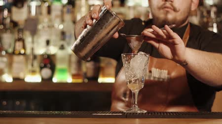 straining : Experienced barman is straining cocktail through small sieve. He is filling glass for customer for bringing it, close-up Stock Footage