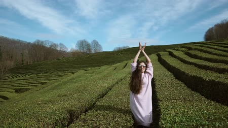 elevação : a young woman in sunglasses pods up against a background of green tea plantations, a lady raises her hands up, behind her long tea fields