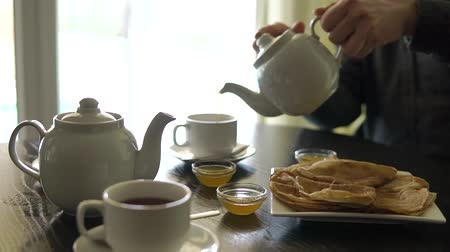 brew tea : close up shot of the mens hands, who pours hot tea from a teapot with porcelain cups, on the table are freshly baked pancakes and a container with honey Stock Footage