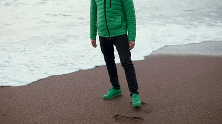 sırt çantasıyla : an adult man who wears an autumn jacket strolls along the sandy beach, the man imperceptibly crouches his foot in the sea foam, the wave hit him in the shoe